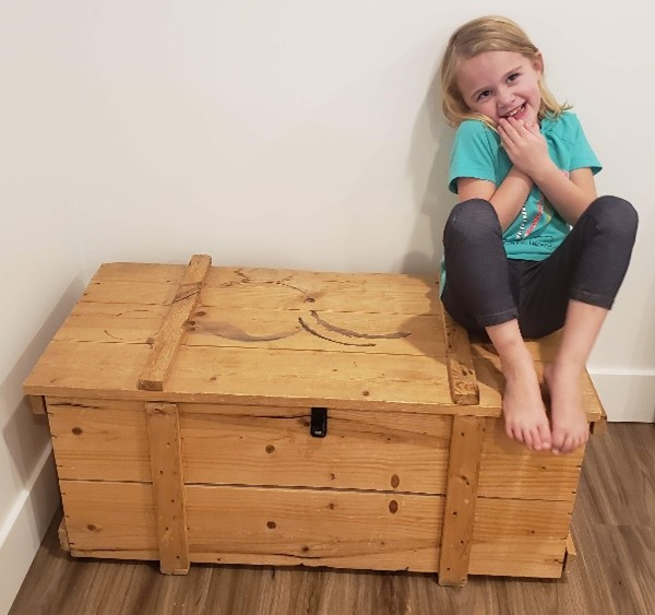 My granddaughter atop a toy box I built many years ago.